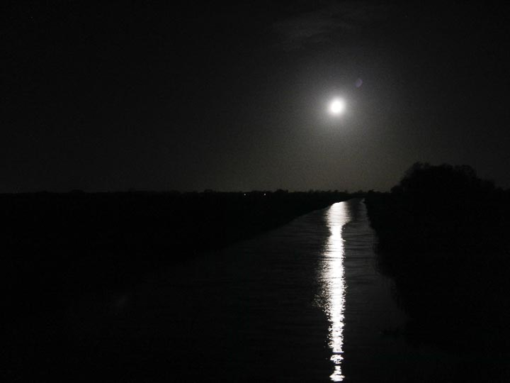 Three-quarter moon over Burwell Lode from the footbridge